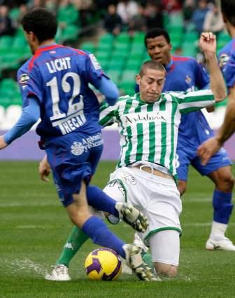 Damiá y Licht pugnan por un balón con el césped mojado.  Foto: Antonio Pizarro