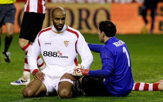 El meta vasco, Iraizoz, conversa con Kanoute en el suelo tras la entrada sufrida por el mali   Foto: Antonio Pizarro