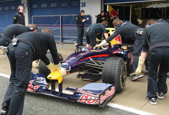 Sebastien Vettel, con el monoplaza de 2009, entrando en boxes. Los mecánicos usan guantes para evitar las descargas que produce el nuevo sistema 'Kers'.  Foto: J. C. Toro