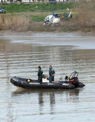 Un helicóptero de la Policía sobrevuela la zona de búsqueda en el Guadalquivir, donde se encuentra una lancha de la Guardia Civil. / Juan Carlos Vázquez
