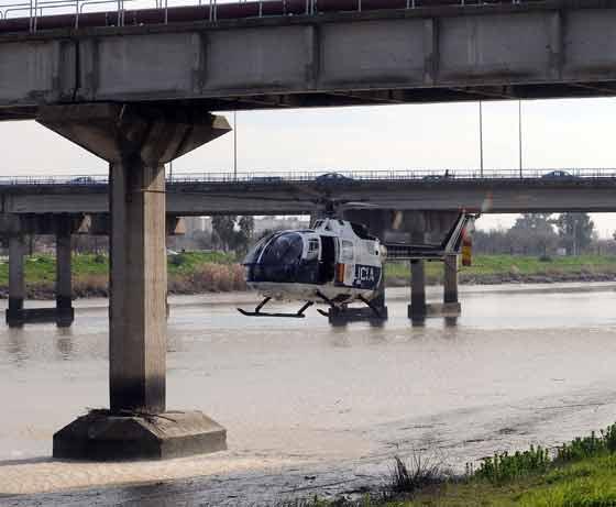 Un helicóptero de la Policía sobrevuela la zona de búsqueda en el Guadalquivir. / Juan Carlos Vázquez