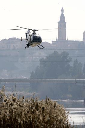 Un helicóptero de la Policía sobrevuela la zona de búsqueda en el Guadalquivir. / Antonio Pizarro