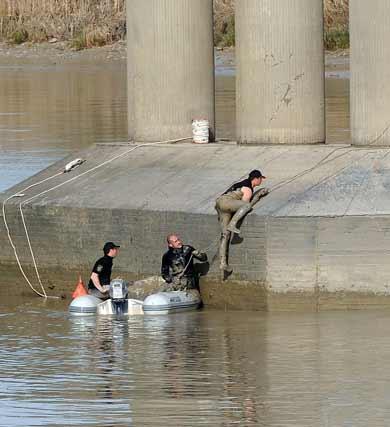 Uno de los miembros del dispositivo sube por uno de los pilares de la pasarela. / Juan Carlos Vázquez