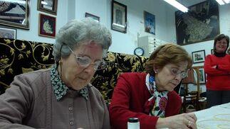 Ángeles Moya, hermana número 1 y Esperanza Martínez, camarera de la Virgen, dan la primera puntada.  Foto: J.P.