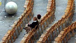 Dos mujeres no dudan en llegar con premura para conseguir un buen sitio desde donde observar las procesiones en calle Larios.   Foto: Sergio Camacho