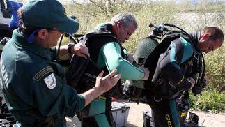 Un agente de la Guardia Civil ayuda a los buzos a colocarse la bombona de oxígeno.  Foto: Juan Carlos Muñoz