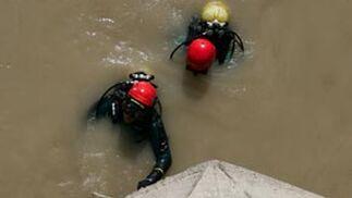 Un agente de la Guardia Civil ayuda a los buzos a salir del agua.  Foto: Juan Carlos Muñoz