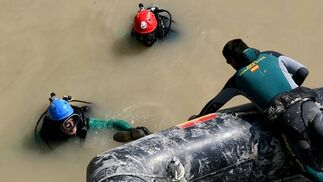 Un buzo saca del turbio río una bota localizada en el rastreo y se la da a otro buzo que espera en la lancha.  Foto: Juan Carlos Muñoz