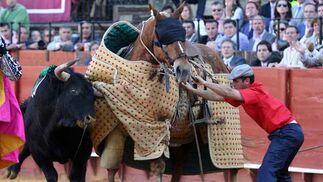 Un caballo es ayudado ante la embestida por parte de un toro.  Foto: Juan Carlos Muñoz