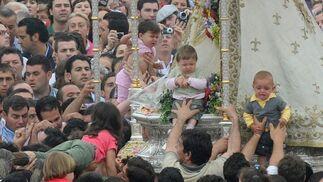 El 'vuelo de los niños'a manos de los costaleros para ser acercados lo más posible a la Virgen pidiendo para ellos su protección.  Foto: AFP