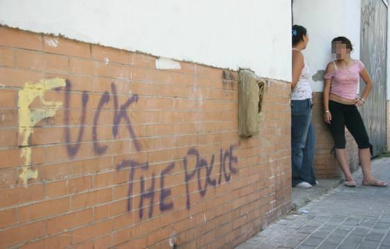 Varias jóvenes conversan en el exterior del edificio en cuya fachada aparecen pintadas insultantes en inglés.  Foto: Belén Vargas, Jaime Martínez