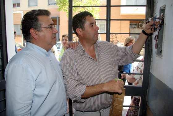 Vicente Vega, uno de los vecinos que pagan los 16 euros de comunidad, muestra a Zoido el estado del porterillo.  Foto: Belén Vargas, Jaime Martínez