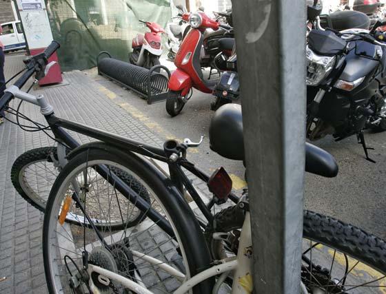 Los ciclistas optan por atar las bicicletas en las señales de tráfico al tener inhabilitado por la moto el amarradero.   Foto: Lourdes de Vicente