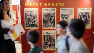 Unos chavales miran las portadas expuestas en el Salón del Apeadero.