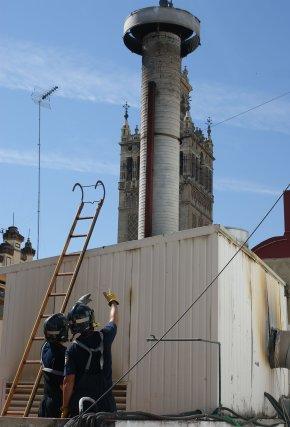 Dos bomberos observan la chimenea donde se provocó el humo.  Foto: Marisa Rivera