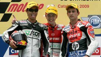 Los pilotos de 125 cc Andrea Iannone (c), Nico Terol (i) y Sergio Gadea celebran en el podio el primero, segundo y tercer puesto, respectivamente.  Foto: Efe