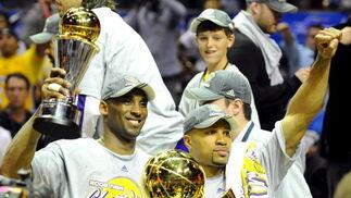 Bryant (i) y el base Fisher (d) muestra las copas de MVP de la final y campeón de la NBA, respectivamente.