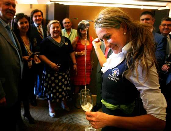 La venenciadora de los vinos del Condado (Huelva) demuestra su habilidad en presencia de la consejera de Agricultura y su comitiva.  Foto: Pascual