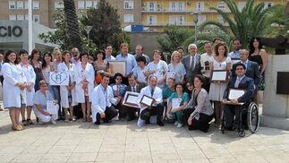 Los premiados, con el Equipo de Coordinación de Trasplantes de Sevilla y Huelva, y los presidentes de las asociaciones de trasplantados, junto al Monumento al Donante de Órganos, en el Hospital Virgen del Rocío.  Foto: Victoria Ramírez