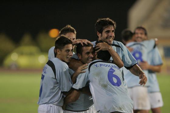 Los jugadores del Poli abrazan al centrocampista por su gol.   Foto: Javier Alonso