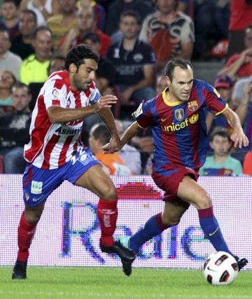 Iniesta corre perseguido por un rival. / EFE