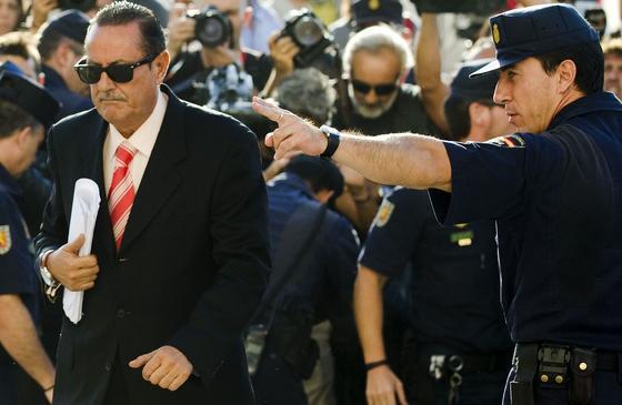 Un olicía nacional indica alel ex alcalde de Marbella Julián Muñoz el camino de entrada a la Audiencia Provincial.