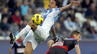 El defensa del Málaga Weligton salta para conseguir el control del balón ante el delantero del Racing Markus Rosenberg.  Foto: Jorge Zapata/EFE