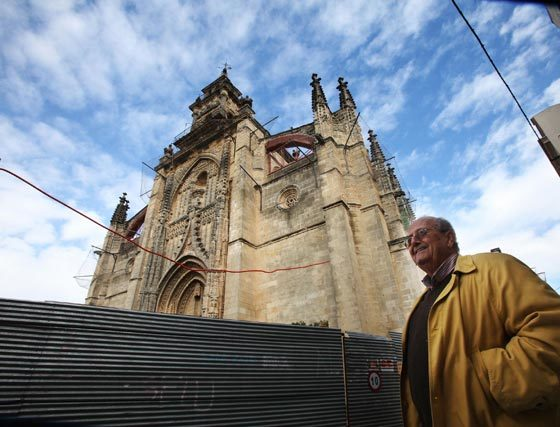 El cura de Santiago, Pedro de la Herrán, ante la parroquia y su cobertura de redes, vallas y andamios.    Foto: Vanesa Lobo