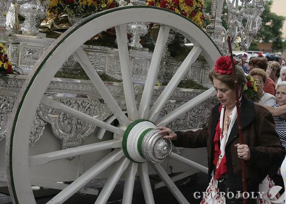 Una hermana, ataviada de rociera, camina junto a la gran rueda del carruaje del simpecado.  Foto: José Ángel García