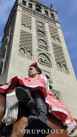 Una jinete, ataviada con traje y calzado de romera, pasa junto a la Giralda.  Foto: Juan Carlos Vázquez