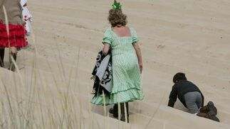 Una peregrina andando por las arenas mientras un niño juguetea a su lado.  Foto: Pascual