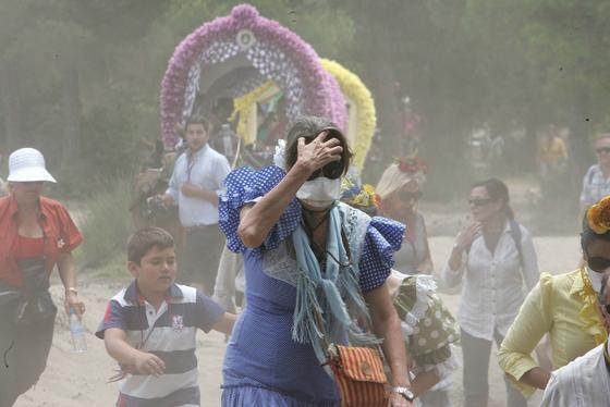 Una romera se protege del polvo del camino con una mascarilla   Foto: Pascual