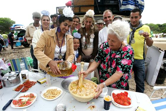 Una veterana rociera prepara la comida con el apoyo de un animado grupo durante el rengue de almuerzo por los parajes del Coto de Doñana.   Foto: Pascual