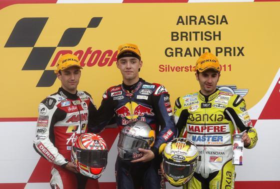 El piloto francés Johann Zarco, segundo; el alemán Jonas Folger, vencedor, y el español Héctor Faubel, tercero, en el podio de 125 cc del Gran Premio de Gran Bretaña.  Foto: EFE