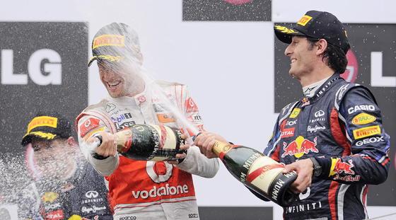 Jenson Button celebra la victoria en el Gran Premio de Canadá con Mark Webber y, al fondo, Sebastian Vettel.  Foto: AFP Photo
