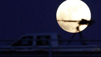 Con la luna al fondo antes del eclipse, pasa una camioneta en Libia, zona de guerra.  Foto: Agencias