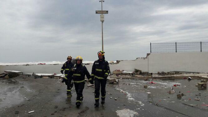 Bomberos en el muro derrumbado por el temporal.