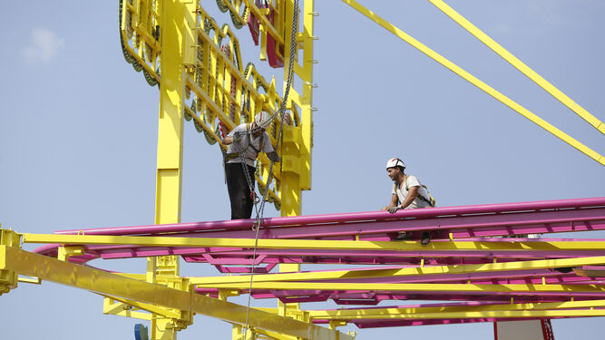 Operarios de una montaña rusa, en la parte alta de las vías desmontando.