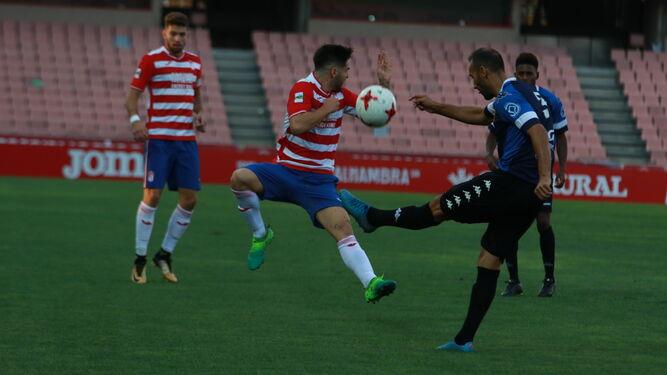Un jugador del Granada B se interpone en el despeje de un futbolista del Mérida en un duelo de la presente temporada.