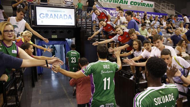 1. Jugadores del Unicaja de Málaga saludan a la afición que espera para chocar las manos. 2. La afición respondió y llenó la parte baja del Palacio de los Deportes, aunque con algunos asientos vacíos. 3. Los representantes deportivos, políticos e institucionales posan en la presentación del torneo.