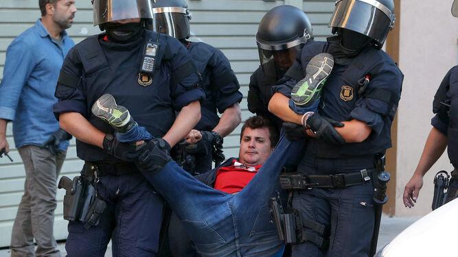 Varios mossos desalojan a un joven.