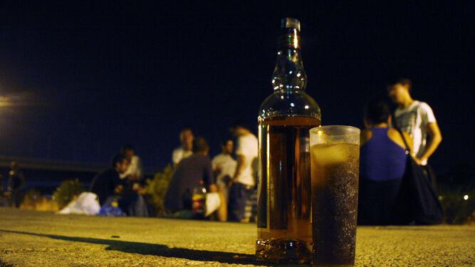 Varios jóvenes beben en una 'botellona' junto al río Guadalquivir.