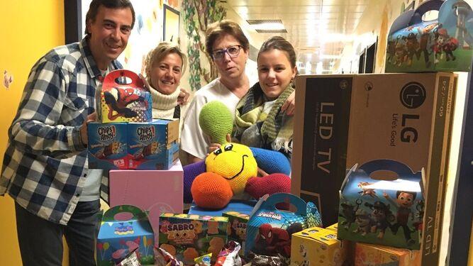 En la planta séptima del Maternal Candela, su familia  y personal sanitario con material para los menores de oncología.