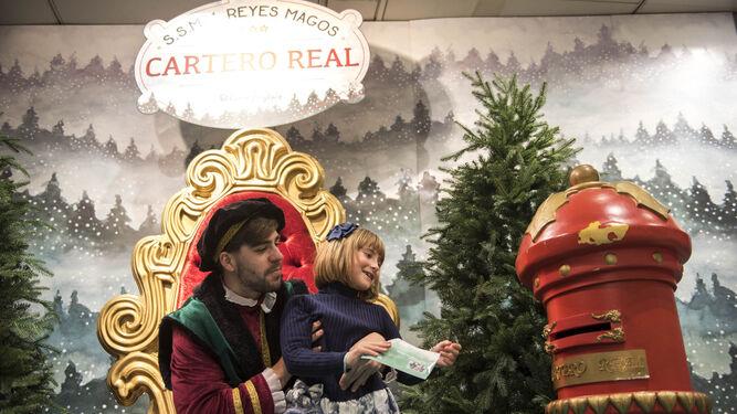 El cartero real ayuda a una pequeña a hacer llegar su petición a los Reyes Magos de Oriente.