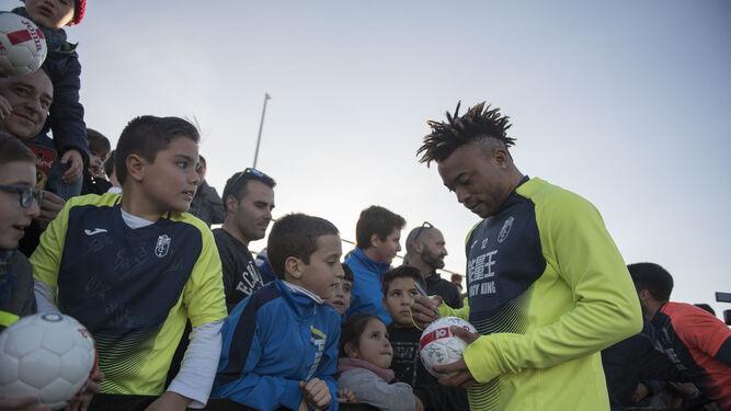 El camerunés Pierre Kunde, uno de los jugadores más aclamados, firma mientras le contemplan con admiración.
