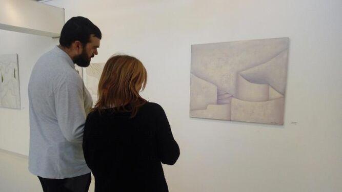 Dos personas admiran la obra de la pintora y escritora Rosaura Alvárez.