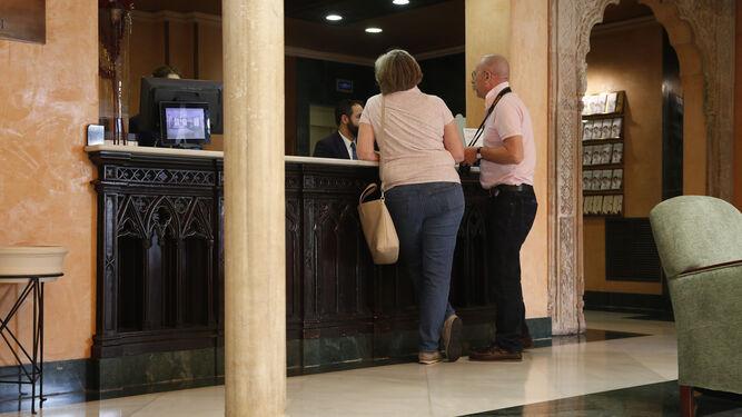 Una pareja de turistas se registran en un hotel del centro.