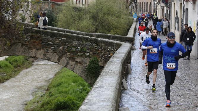 Los atletas, a su paso por la Carrera del Darro, uno de los puntos más bellos de todo el recorrido de la carrera.