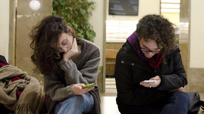 Estudiantes consultan su móvil a las puertas de la Facultad.