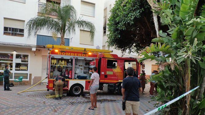 Bomberos y vecinos observan el bloque incendiado.